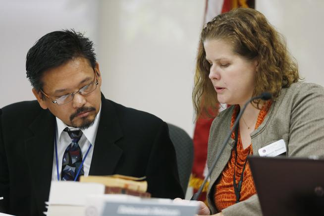 Dr. Ray Estacio, a member of the Colorado Board of Health, confers with Deborah Nelson, board administrator, during testimony to add post-traumatic disorder to the list of ailments eligible for treatment with medical marijuana during a hearing before the board in Denver. (David Zalubowski, AP)