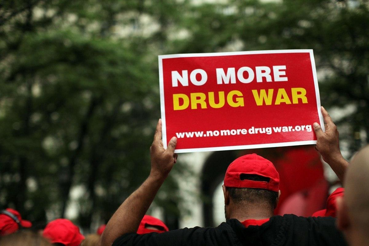 Image of protester hold sign to end the war on drugs