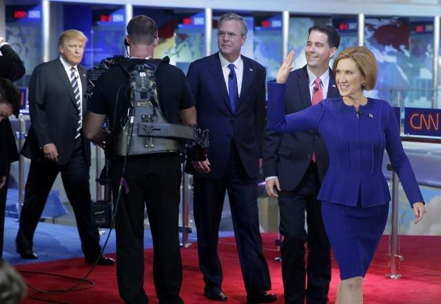 Republican presidential candidate Carly Fiorina, leads fellow candidates Scott Walker, Jeb Bush and Donald Trump as they take the stage prior to the CNN Republican presidential debate on Wednesday, Sept. 16, 2015. (AP Photo/Chris Carlson)