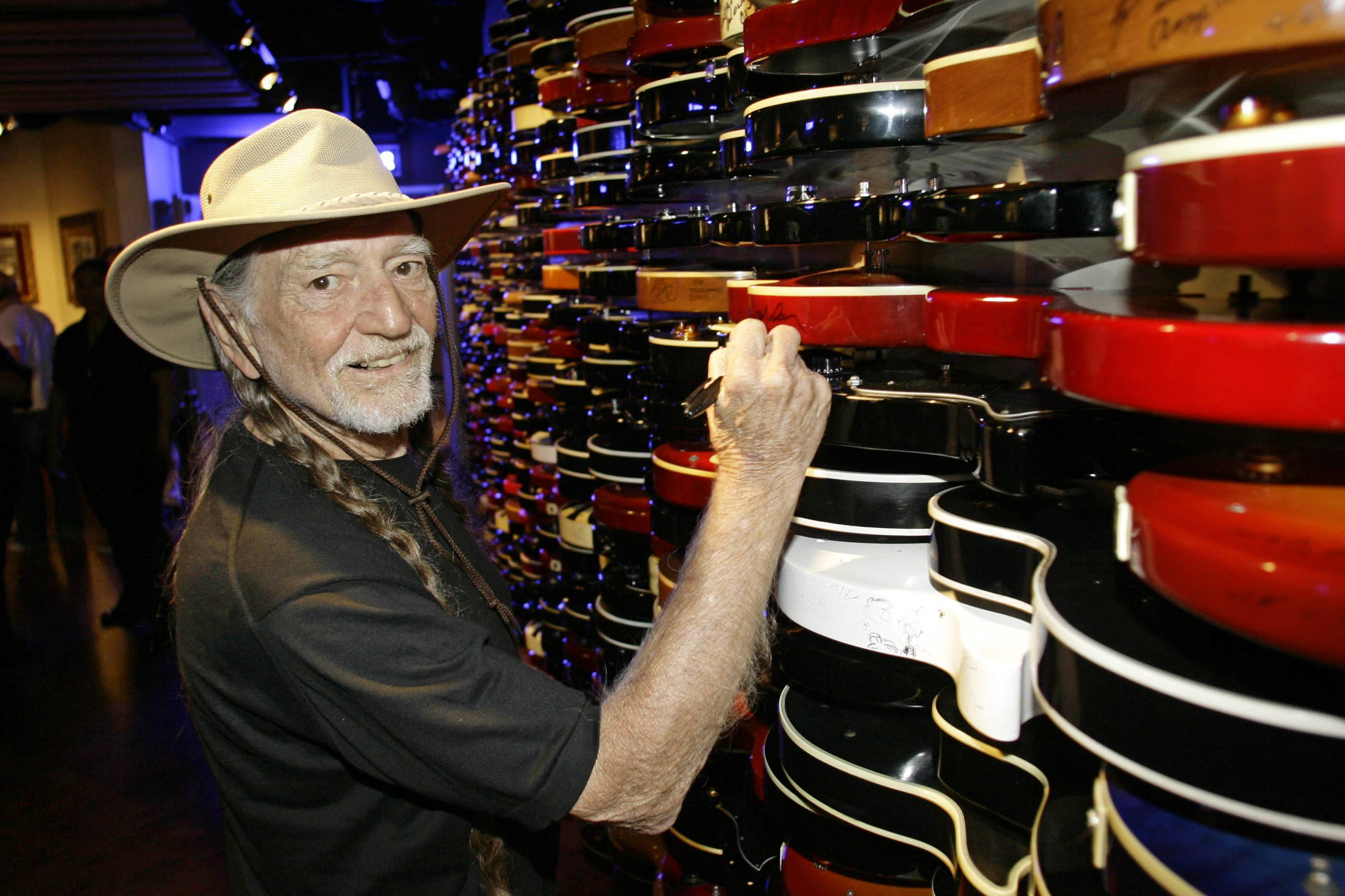 Image of Willie Nelson autographing guitars